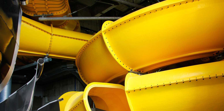 Detaljbild på en gul vattenrutschkana i kokpunkten simhall